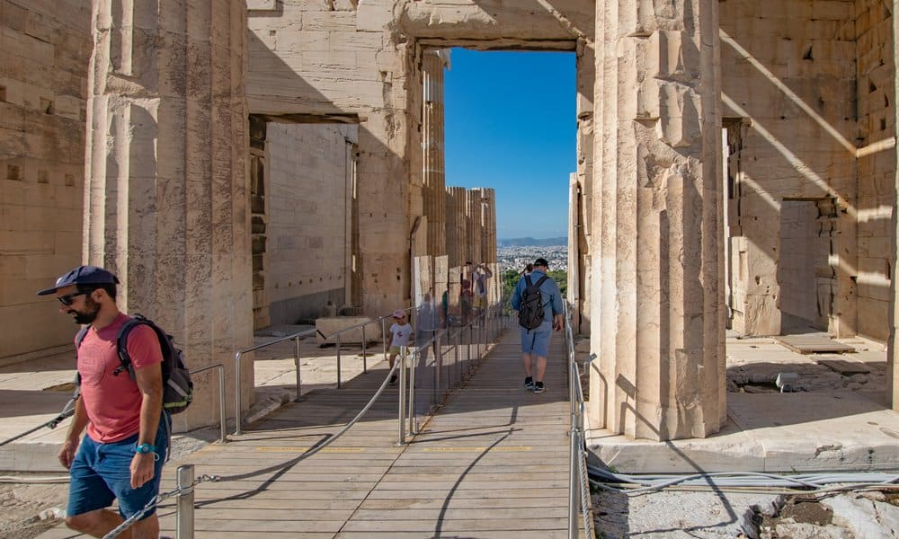 A perspex barrier divides people entering the Acropolis from those exiting.