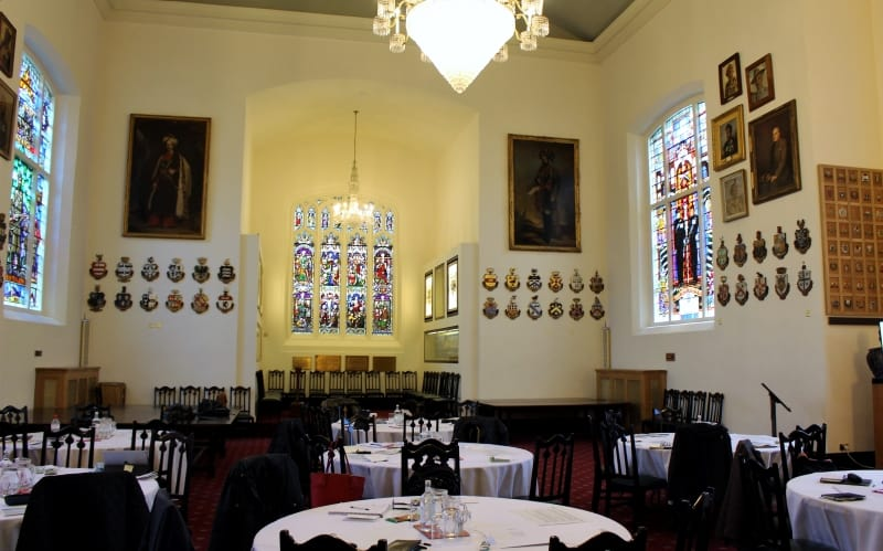 The indian Memorial Room with a large chandelier, paintings on the walls and stained glass windows.