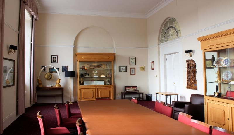A wide shot of the International Room showing display cases and artwork ont he walls around a large dining table.