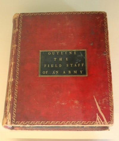 A close up of a red bound book which was Le Marchants Manual and is now in a display case in Sandhurst.