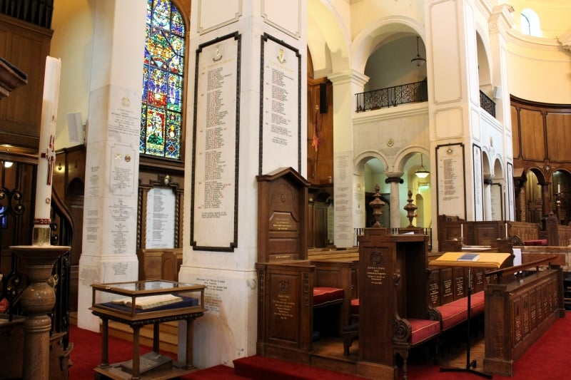 The interior of the Memorial Chapel at Sandhurst showing names carved on the walls and pews.