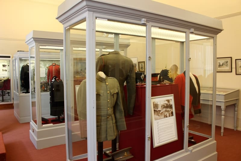 Display cases filled with uniform and objects inside the RMAS Museum room at Sandhurst.