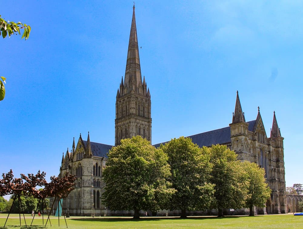 Salisbury Cathedral with artwork and trees in front of it.