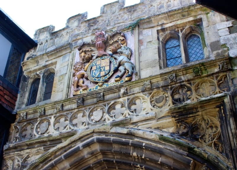 A close up of the coat of arms on the High Street Gate.