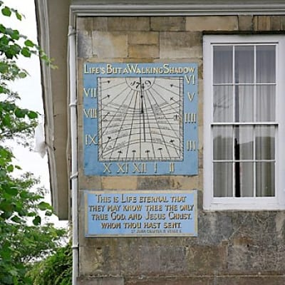 A close up of the sundial on the wall of Malmesbury House in the cathedral close in Salisbury.