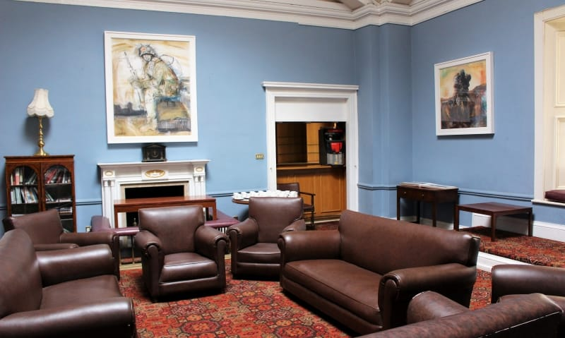Inside Toppers Bar showing the chairs and sofas with artwork on the walls in RMA Sandhurst.