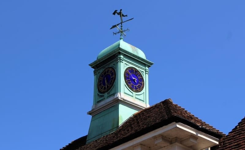 A close up of the WH Smith clock in Salisbury on top of a roof against a blue sky.