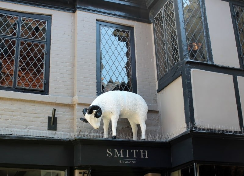 A close up of a model of a ram above a shop doorway.