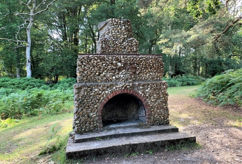 A flint fireplace on a concrete base standing alone in a forest.