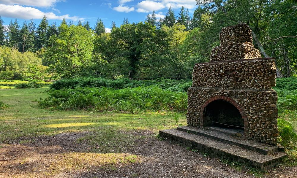 A stone fireplace standing alone in the New Forest, which acts as a war memorial.