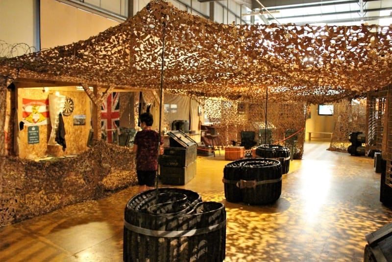 A re-creation of a post in Afghanistan under camouflage cover with a boy walking past the displays.