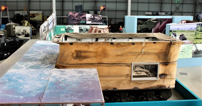 A DD Sherman tank with its screen raised in a simulated sea scene.