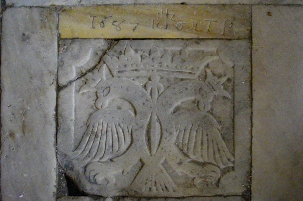 Marble slab on the floor depicting the double-headed eagle and the date 1687.
