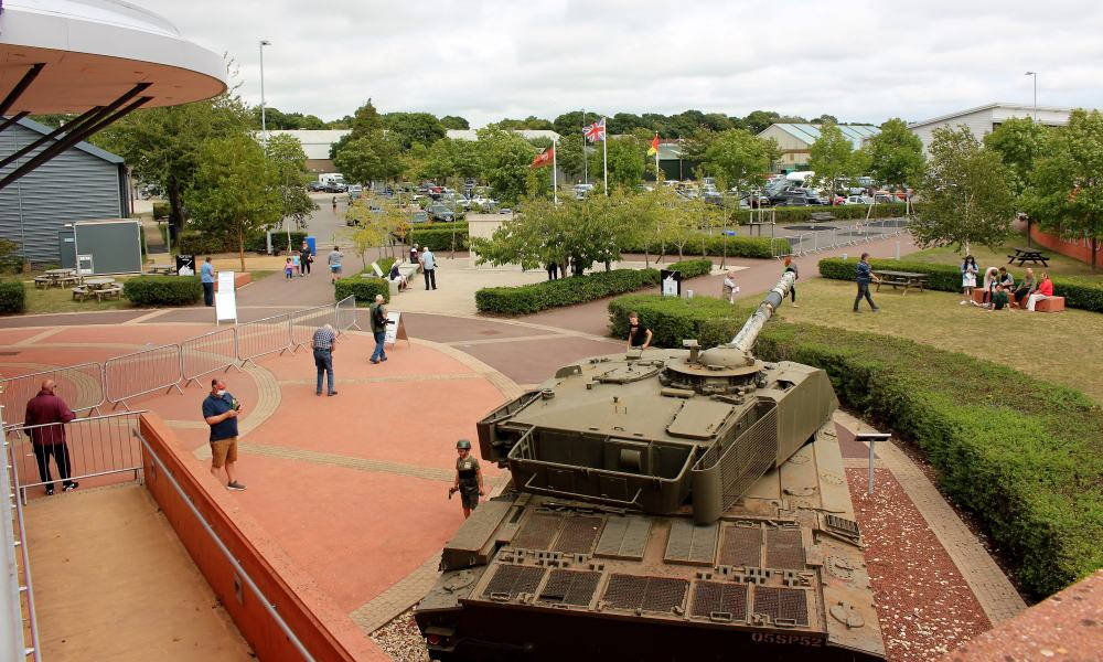 The outside of the tank museum showing a tank, people and a memorial.