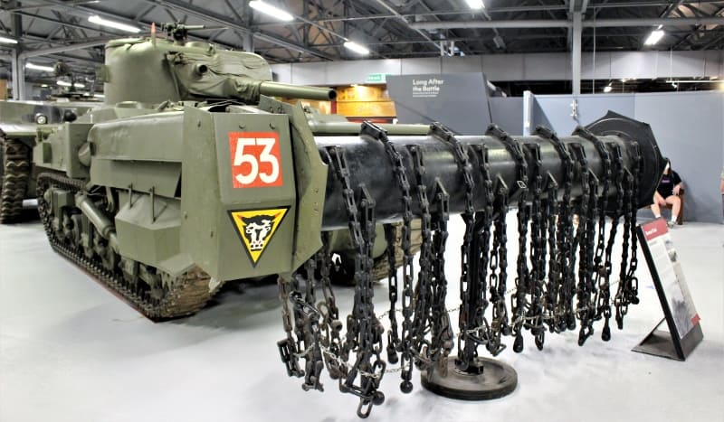 A  tank with a roller at the front with metal chains attached to it.
