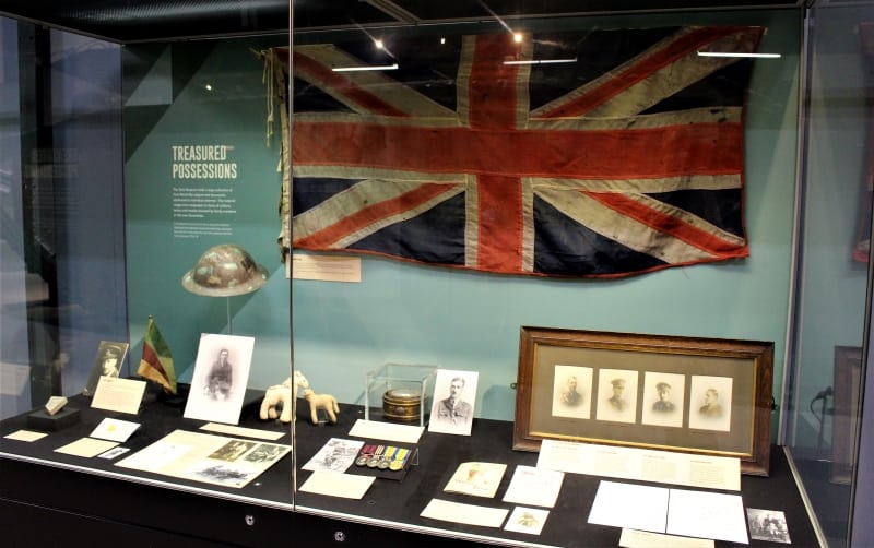 A  display case with a British flag, documents and other small objects under the heading of 'Treasured Posessions'