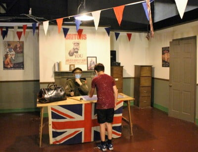A re-creation of a recruitong office in World War I with a boy standing in front pretending to sign up.