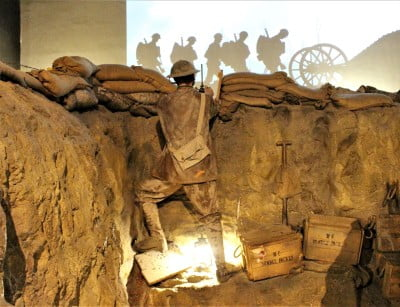 A re-creation of a World War I trench with a mannequin soldier climbing out.