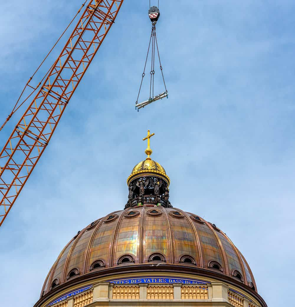 The cupola and cross having just been lowered into place on the dome above the entrance of the Humboldt Forum in Berlin.