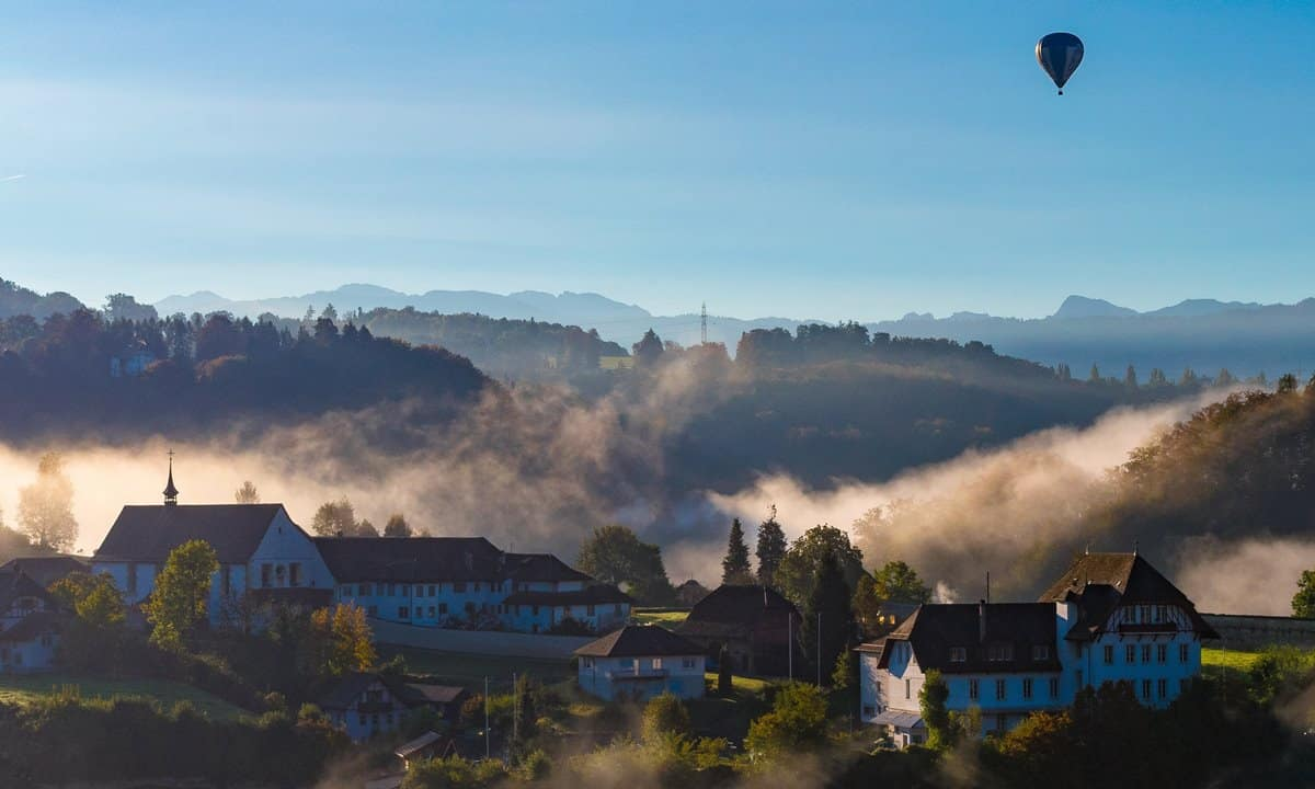 A hot air balloon floats over a small German town shrouded in dawn mist.