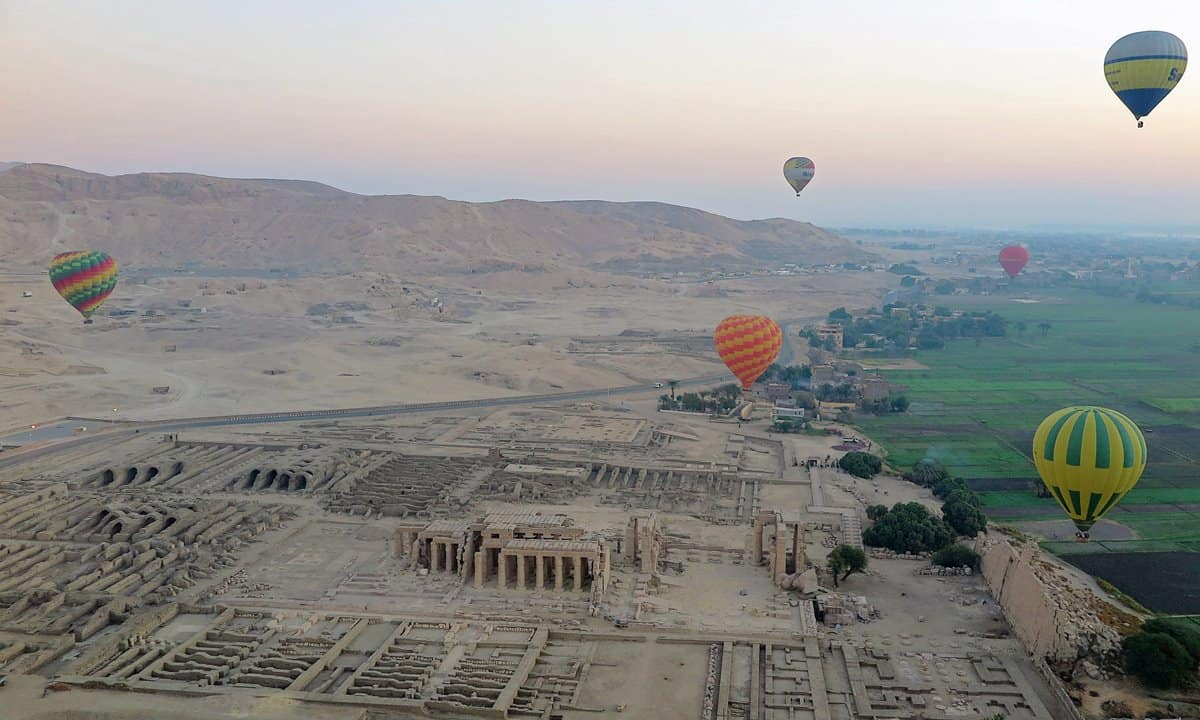 Hot air balloons float above the Ramesseum on the west bank of Luxor at dawn.