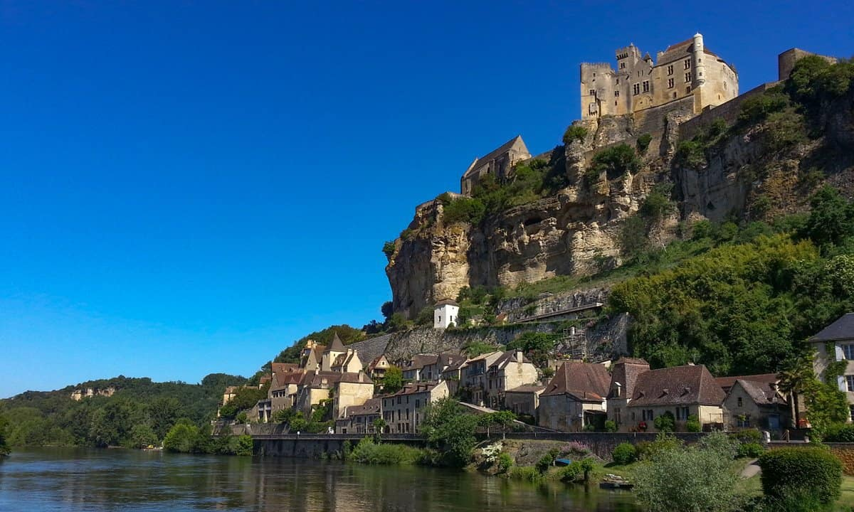 Beynac castle is sited at the very edge of a sheer limestone cliff above the Dordogne River.