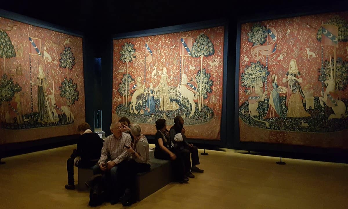 Visitors sit in the darkened gallery in which the 'Lady and the Unicorn' tapestries are displayed.