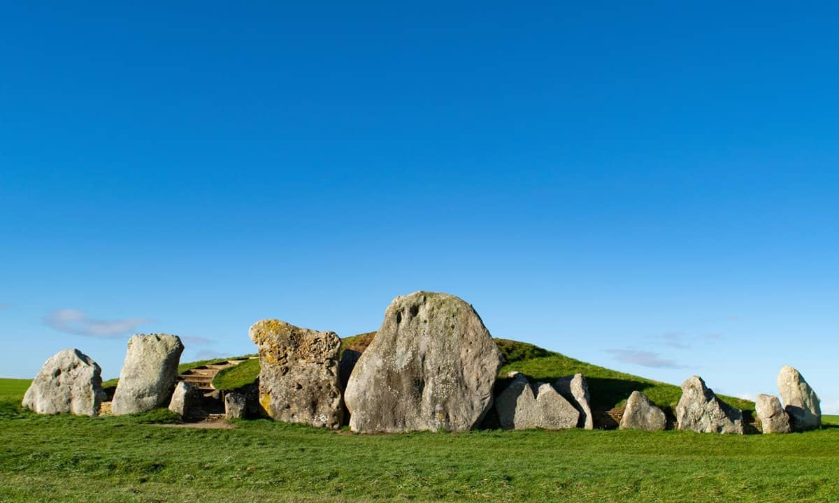 Entrance stones to West Kennet Long Barrow against a brilliant blue sky.