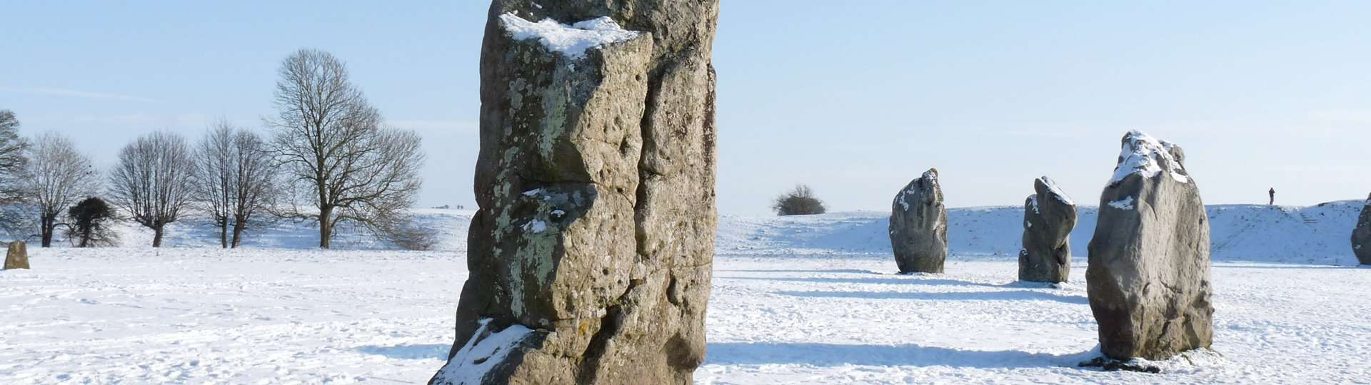 Avebury stone circle covered in snow with a bright blue sky.