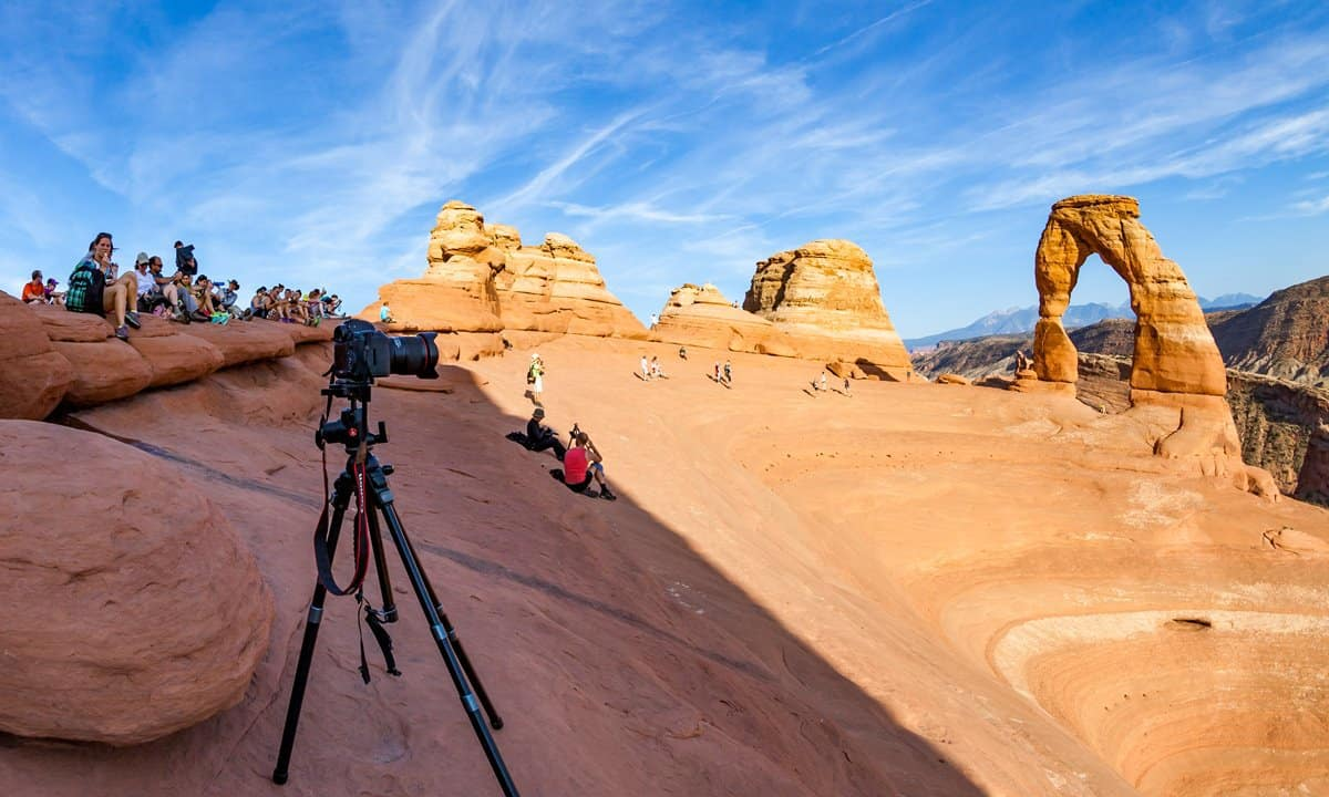 Crowds gather to watch the sunset at Delicate Arch.