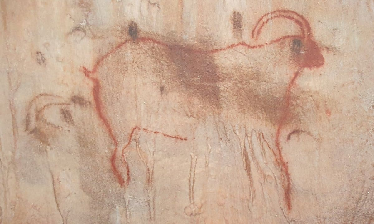 A red outline of an ibex in the Ice Age cave of Cougnac, France.