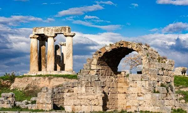 Temple of Apollo behind the ruins of shops in the ancient city of Corinth.