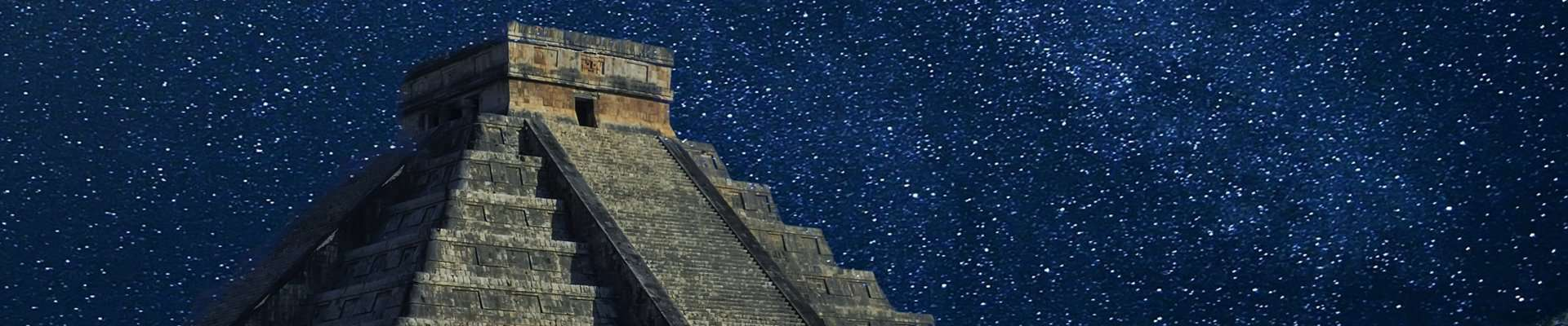 The top of Temple of Kukulcán at Chichen Itza against a stary sky.