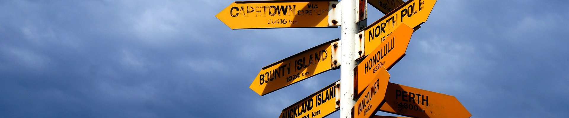 Directions signpost to different cities around the world.