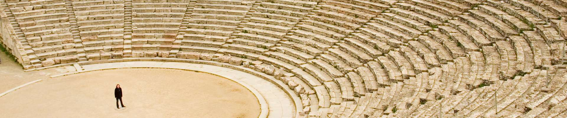 A person stands in the arena of the ancient theatre at Epidaurus, Peloponnese.
