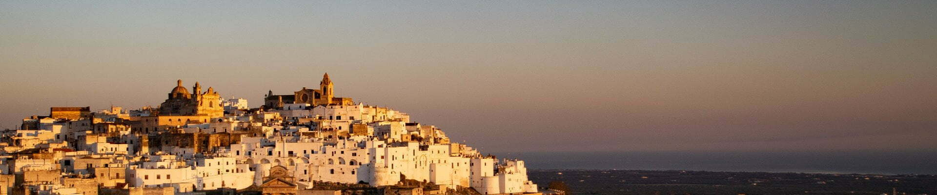 Dawn lights up the white walls of the historic hilltop town of Ostuni in Puglia.