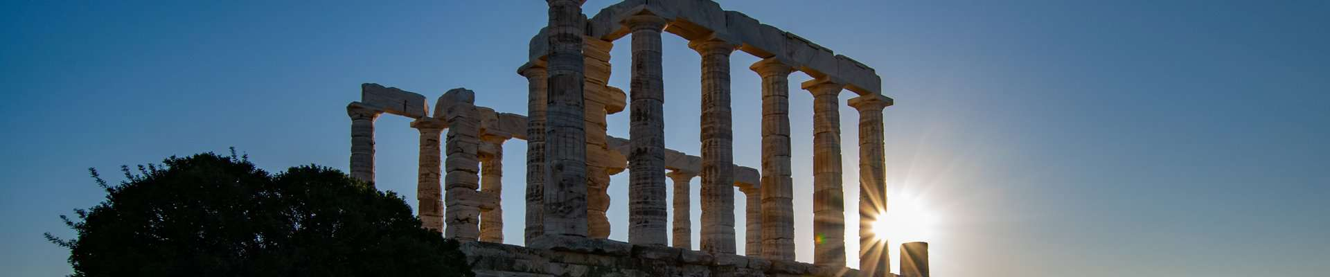 The sun setting behind the Temple of Poseidon at Cape Sounion.