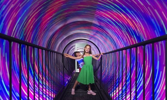 Children walking through the vortex tunnel at the Museum of Illusions in Athens.