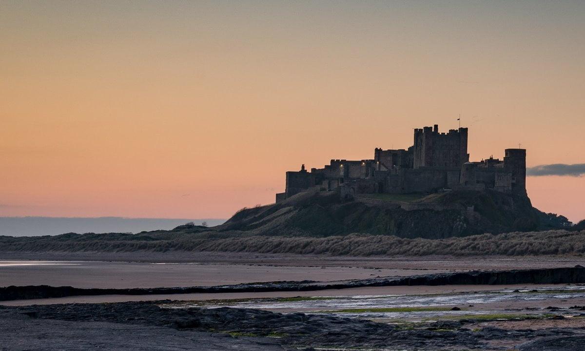 A dawn silhouette of Bamburgh Castle on Bamburgh Beach.
