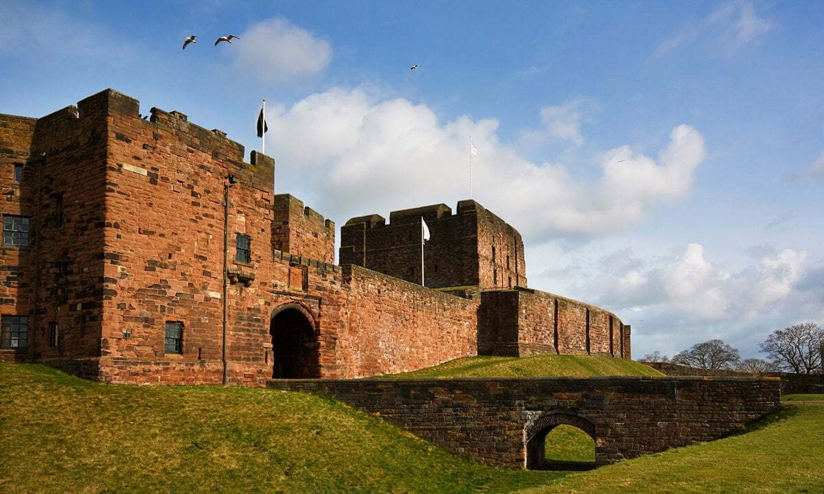 Birds flying above the outer gatehouse that marks the entrance to Carlisle Castle, Cumbria.