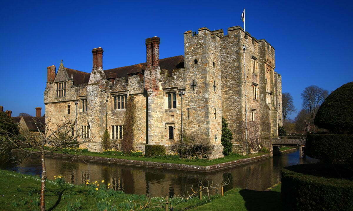 Hever Castle surrounded by an inner moat under a brilliant blue sky.