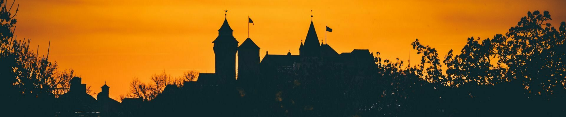A silhouette of Nuremberg Castle at sunset.
