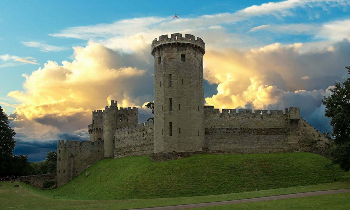 Warwick Castle in front of a dramatic sunset sky.