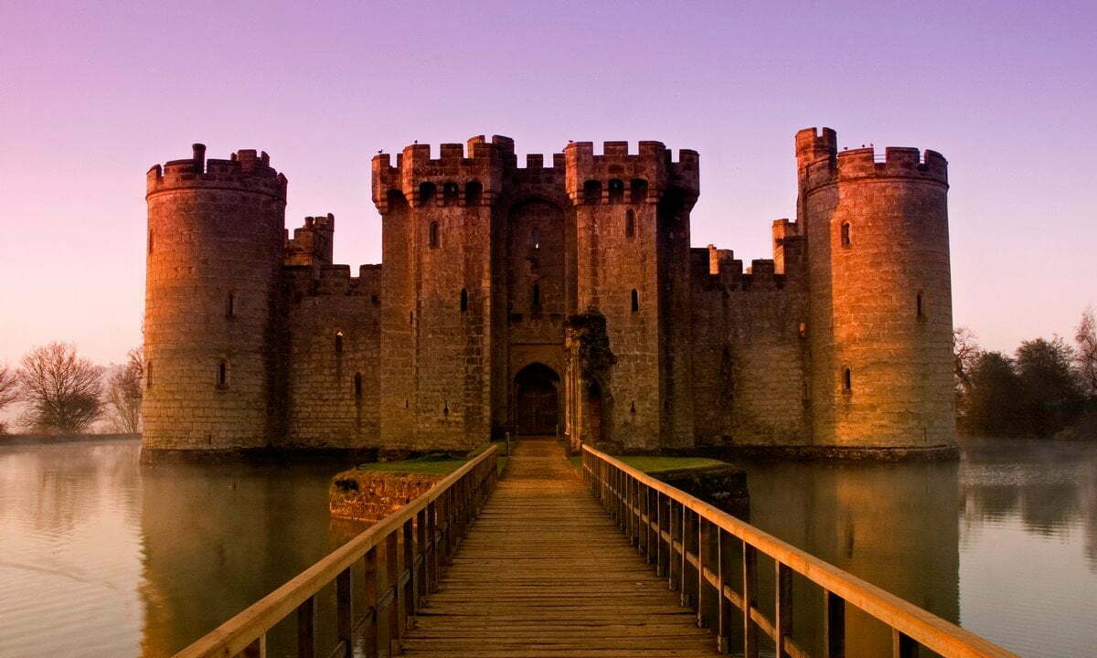 Bodiam Castle on as lightly misty moat at dawn.